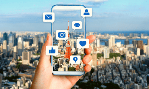 cityscape background with a hand holding a cell phone that has apps jumping out from the screen