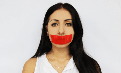 headshot of a woman with red tape over her mouth to symbolize words that should be banned from your business vocabulary