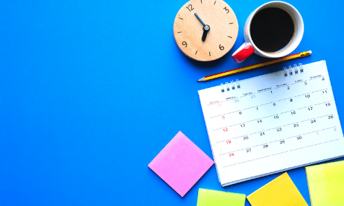 bright blue desk background with various stationary items on top. coffee mug, calendar, and post it notes